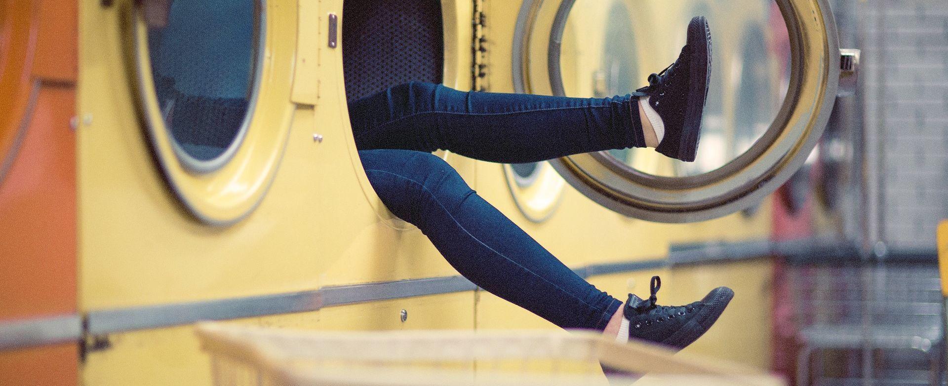 Piernas sobresaliendo de la lavadora