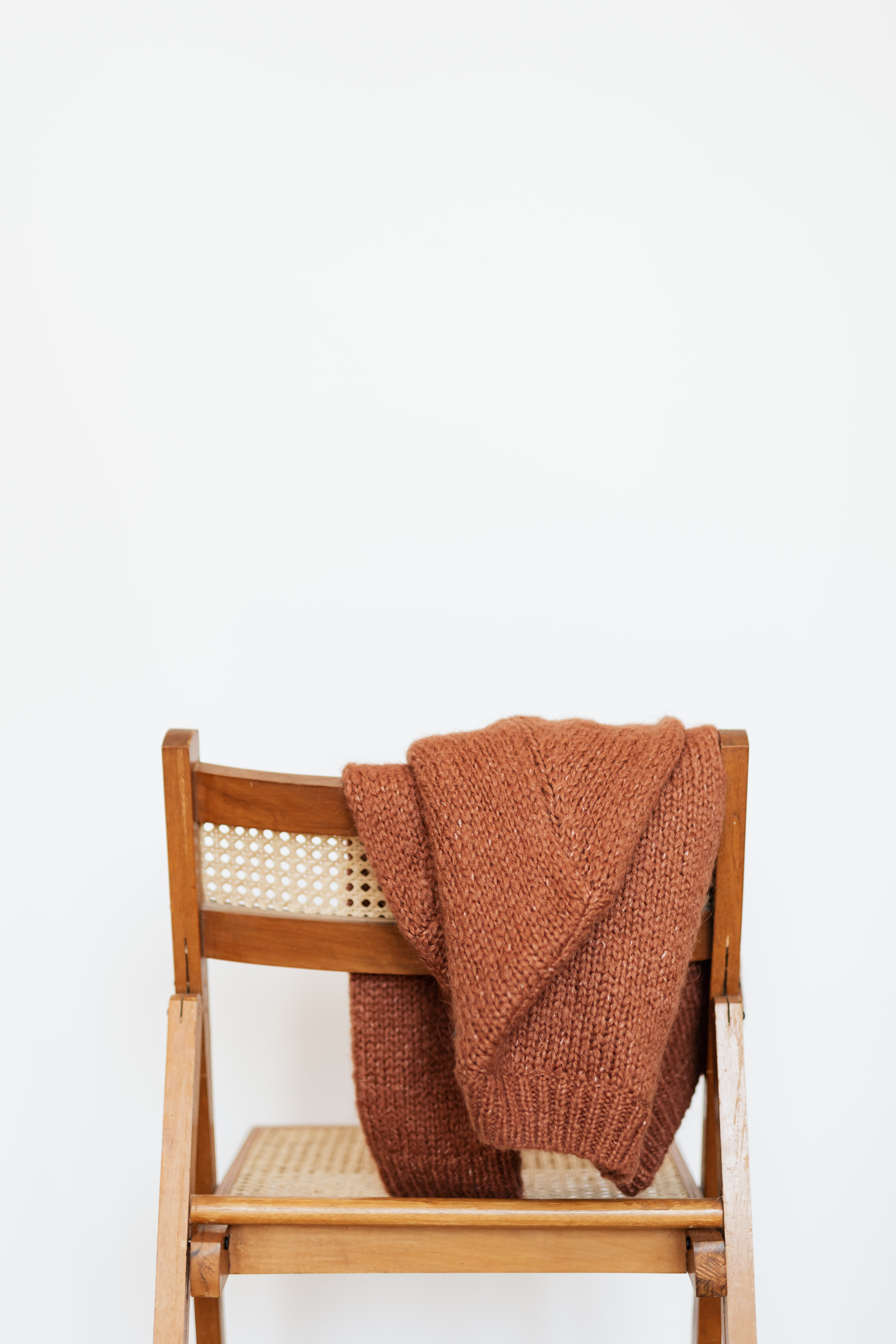 Jersey de lana sobre una silla de madera en una pared blanca